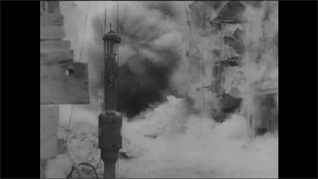 1940s: Tanks and soldiers amass on Normandy beach. Explosions rock city streets. Chimneys collapse in explosion.