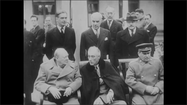 1940s: President Roosevelt, Winston Churchill and Joseph Stalin sit in chairs surrounded by officers.