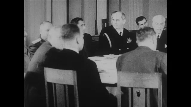 1940s: President Roosevelt, Winston Churchill and Joseph Stalin sit in chairs around meeting table with officers.