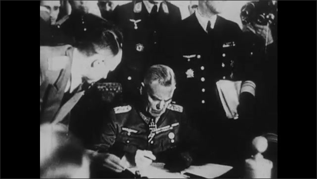 1940s: Nazi generals sign documents of surrender. Swastika explodes on building.