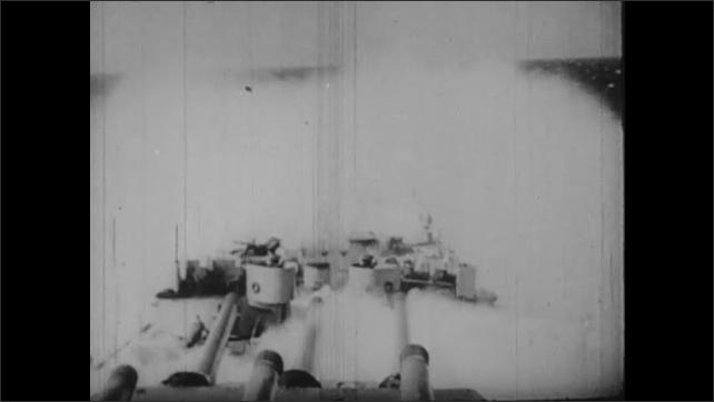 1940s: Waves break over bow of battleship in Pacific ocean.