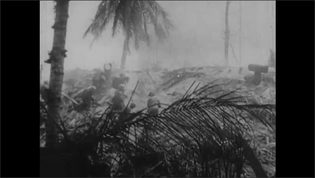 1940s: Marines fight on sands of Tarawa. Soldiers fire guns and flamethrowers at Japanese emplacements.