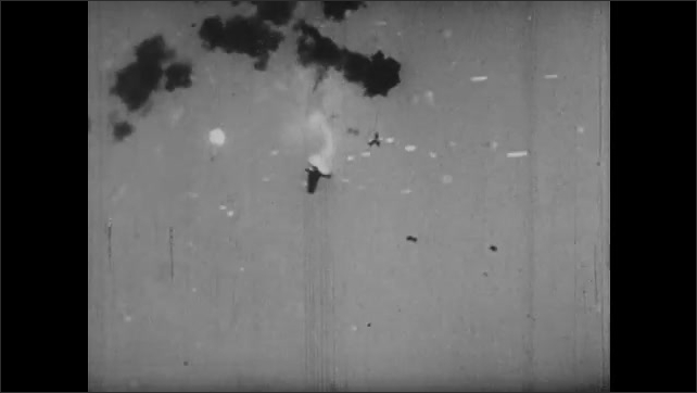 1940s: Explosions in ocean. Flack and explosions in sky. Burning plane spirals down from sky. Plane crashes into the ocean.