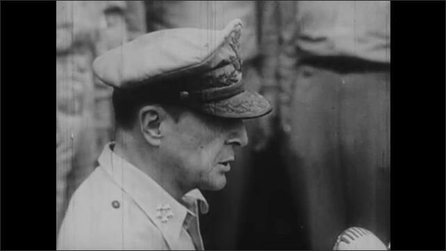 1940s: Japanese generals and representatives stand on deck of battleship. General Douglas MacArthur speaks into microphone.