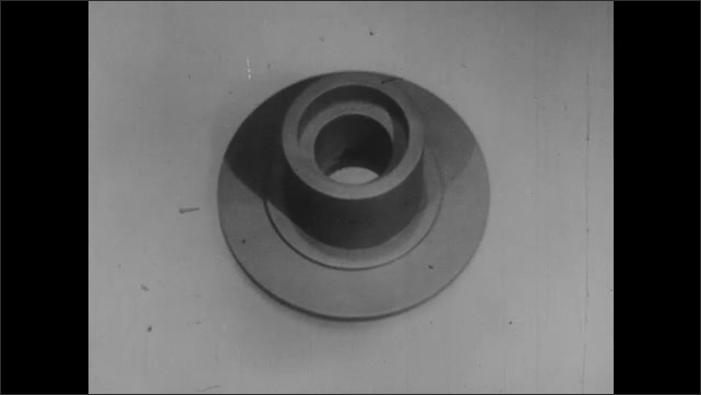 1950s: Cylinder object with flat base. Looking down top of cylinder into hollow circle center. Side of cylinder.