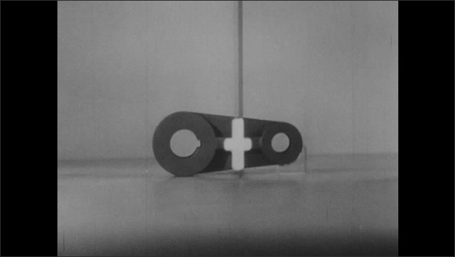 1950s: Illustration of object with two round ends, one large than other, and flat rib in center. Object bisected by plastic piece. White cross appears on object and leaves. Draw of object.