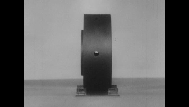 1950s: Round cylinder with holes in it sits in plastic display holder. Piece of clear plastic dissects wheel leaving sectional view. Blueprint illustration of sectional wheel.
