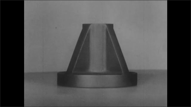 1950s: Cylinder object with webbed ribs ringing around it. Piece of clear plastic bisects object leaving sectional view of cylinder.