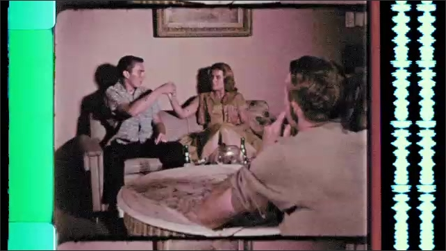 1960s: Teens smoke joint on couch in man's apartment. Man at table speaks and stands up. Girl shakes head and talks to boy on couch.