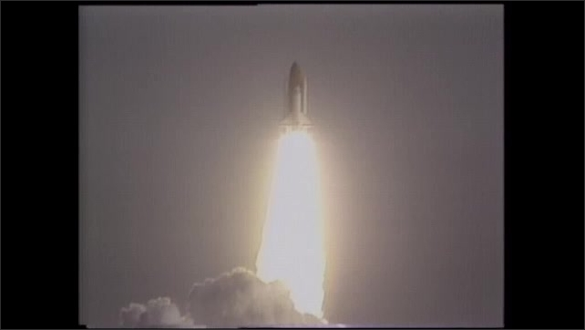 1990s: UNITED STATES: space ship takes off. Slow motion of shuttle launch. Flames behind shuttle in sky.