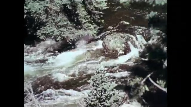 1970s: Mill pond. Men drive freight train cars through mountain tunnel. Fish swim in river. Mining buildings.