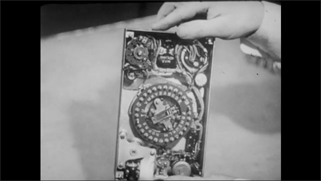1940s: Technical drawing. Man turns machine with knobs and gauges around. Blueprints.