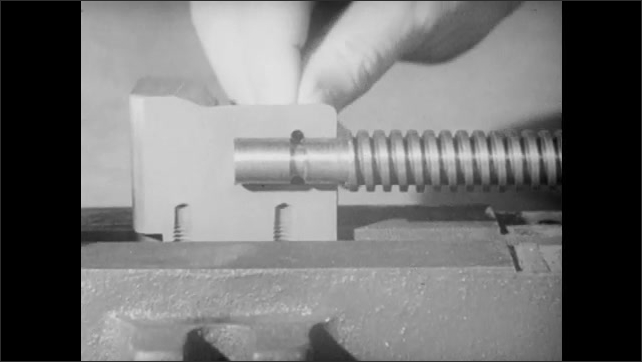 1940s: Technical drawing of clamp part. Man places pin into hole on moveable jaw.
