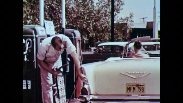 1950s: UNITED STATES: Attendant fills car with gasoline. Attendant takes out hose. Attendant puts hose in tank of car