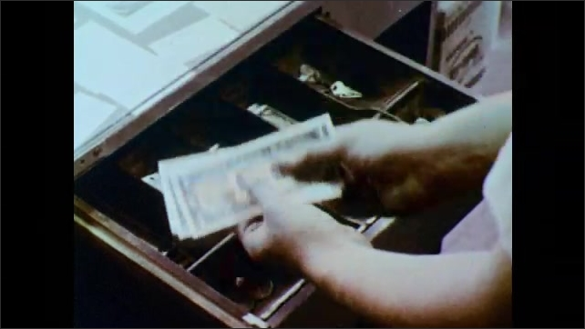 1950s: UNITED STATES: money drawer in station house. Attendant gets change for lady. Lady sits in car. Attendant gives change to lady
