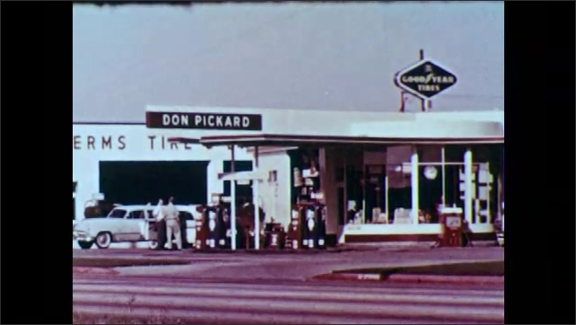 1950s: UNITED STATES: Don Pickard service station. Attendant checks under hood of car. The End title. Pat Dowling Pictures branding.