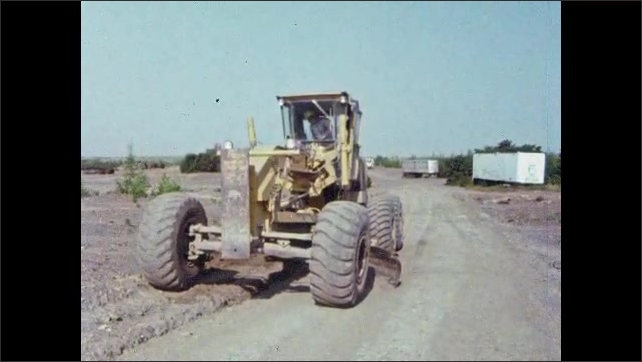 1980s: UNITED STATES: man walks up to digger. Man climbs into cabin. Smoke from machine. Man inside truck