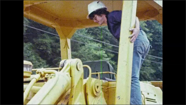1980s: UNITED STATES: men talk by loader. Man climbs into loader. Man sits in cabin of machine