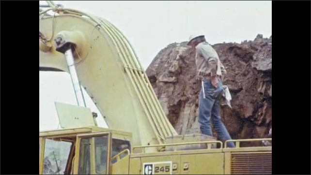1980s: UNITED STATES: men climbs onto top of truck. Man picks up tools. Man climbs up to top of boom.
