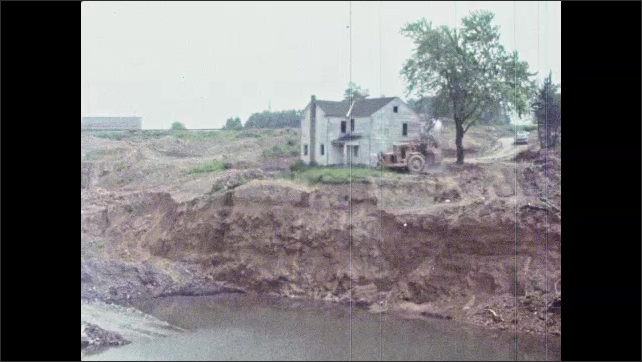 1980s: UNITED STATES: digger drives into building. Man slumped over steering wheel. Hole in side of building