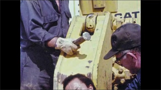 1980s: UNITED STATES: Caterpillar logo on truck. Man with penetrating injury to chest. Man looks at tool. Sparks around welding. Man takes off face mask