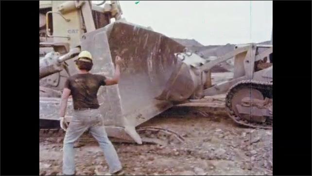 1980s: UNITED STATES: man stands by machines. Machine rolls on gradient. Men run behind machine.