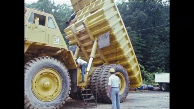 1980s: UNITED STATES: man works underneath hydraulics on truck. Men walk to back of truck