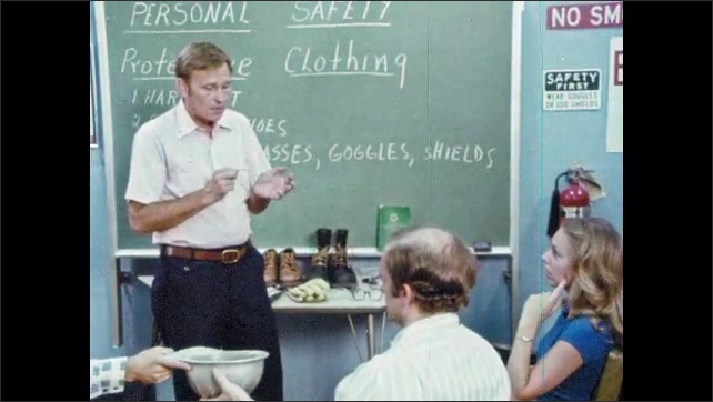 1980s: UNITED STATES: man instructs students in class. Lady puts on hard hat. Man encourages safety consciousness. Protective clothing demonstration.