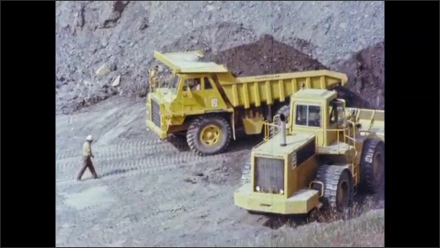 1980s: UNITED STATES: trucks on building site. Man walks to cabin of truck. Operator drives vehicle. Man shouts at driver