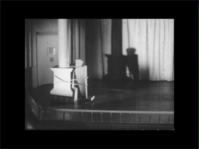 1950s: EUROPE: ENGLAND: post with foliage on theatre stage. View across stage. Model of actor tied to post. Door post on stage