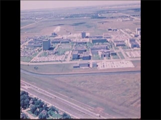 1970s: Johnson Space Center campus. People work in command center.