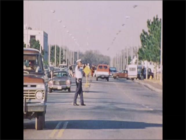 1970s: Young people sit together in a group, ask questions.  Ambulance exits building, police officer directs traffic, doctor examines man. People sit at computer terminals.