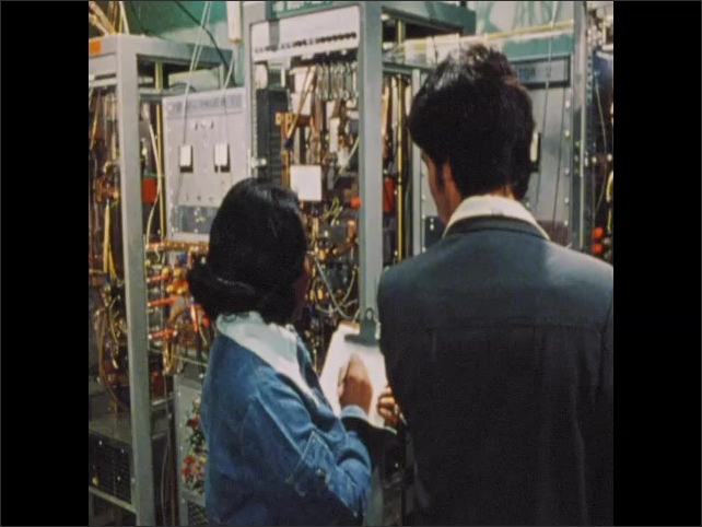 1970s: Man and woman look at cabinets full of cables and wires, check readout on monitor.