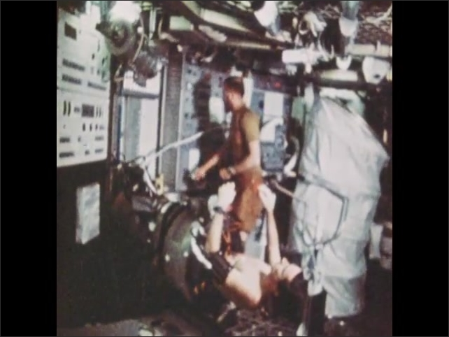 1970s: Skylab spacecraft orbits Earth. Astronaut inside spacecraft lays in tube, man adjusts controls nearby.