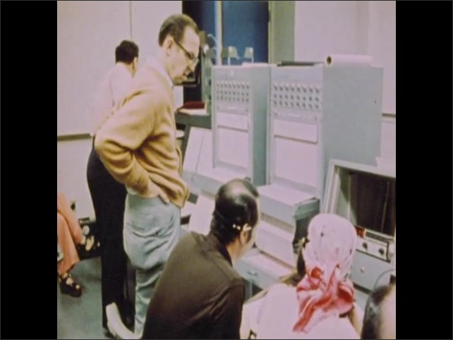 1970s: Men and women monitor computers and equipment.