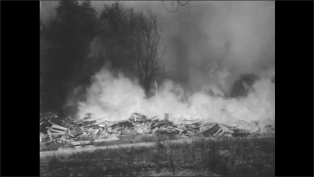 1940s: Flooded houses. Fire along field of rubble. Car pulls into house