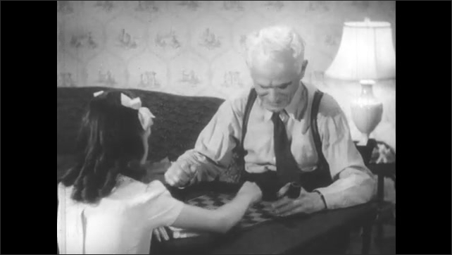 1940s: Family in living room, father at desk, mother sews in chair, daughter and grandfather play checkers, boy reads on couch. Boy sighs while reading. Young girl and grandfather play checkers.