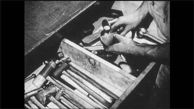 1940s: Man looks through metal forms in drawer, picks up and feels forms.
