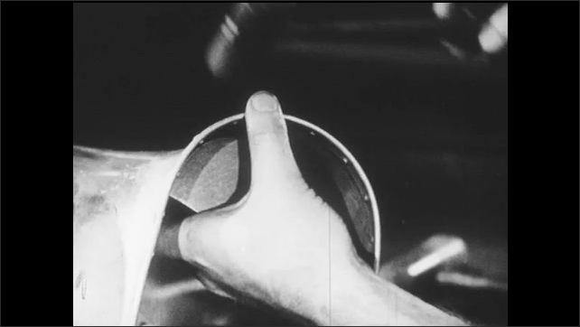 1940s: Man rubs thumb over metal dolly. Man shapes sheet metal with hammer and metal dolly.