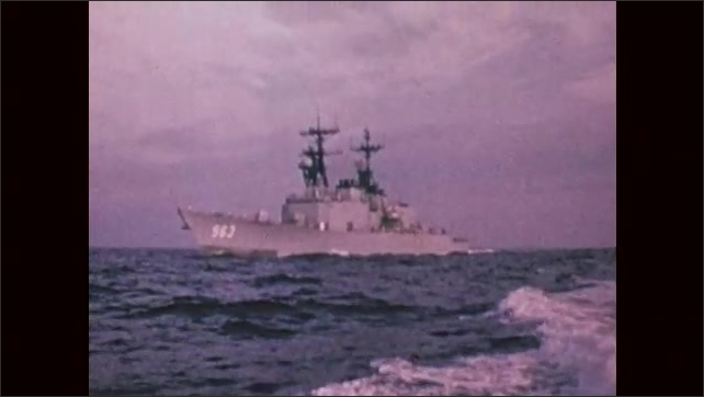1970s: UNITED STATES: USS Spruance (DD-963) in harbour. USS Spruance (DD-963) at sea. Waves on ocean. Front view of ship at sea.