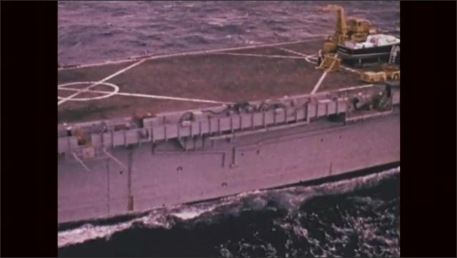 1970s: UNITED STATES: side profile of USNS Matthew Perry (T-AKE-9) at sea. Diggers, boat, and vehicles on deck of ship