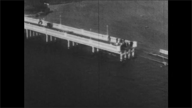 1940s: trolley sits in flood water next to car roofs on city. buildings, houses, bridges, sandbars and land suffer from hurricane damage. men in lifejackets swim in water near shore.