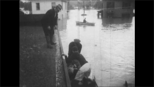 1940s: hurricane waters gather under bridge and streets. rescue boat pulls up to pharmacy as man and dogs on roof step down to police officer. sailors row ship down flood road in town center.