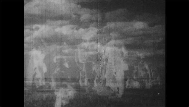 1940s: building debris falls into river near bridge. men march across land. wire fence stretches across landscape. clouds float above ocean. fire burns trees. water floods woods.