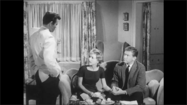 1960s: Young man in white suit with serious look on face. Three young adults in room converse. Man in white suit shrugs and talks.
