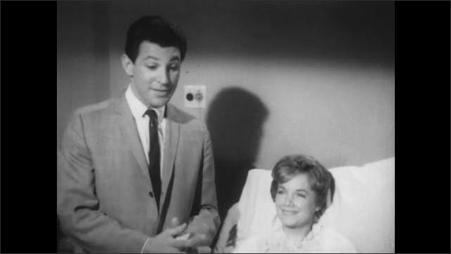 1960s: Man stands next to hospital bed, woman in bed smiling. Man stands next to seated woman, talks. Other couple smile and talk. Man puts hands on seated woman's shoulder, talks.