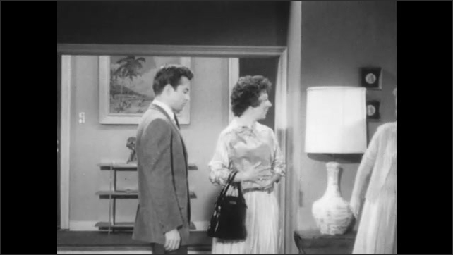 1960s: Young woman opens door to house, older woman enters with paper bag and approaches young man. The three of them talk.