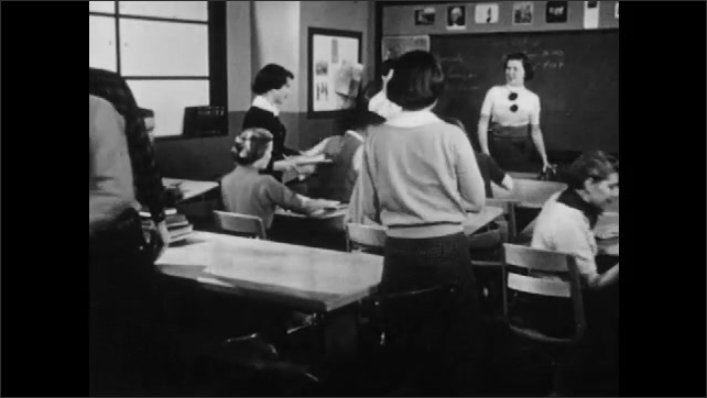 1950s: High school classroom.  Students and teacher stand.  Students leave room.  Girl sits at desk and closes book.