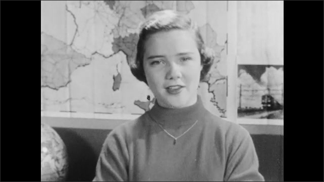 1950s: Classroom.  Teenage girl stands and speaks.