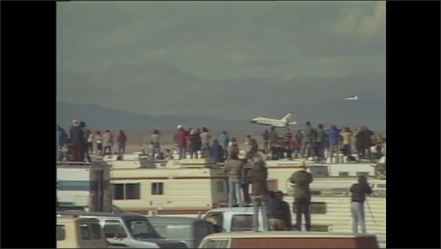 1980s: People look up to the sky and cheer. Space shuttle lands.